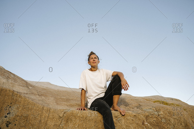 Woman sitting on rock - Offset Collection