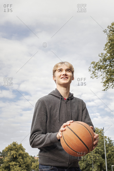 Teenage boy holding basketball - Offset Collection