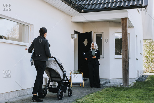 Female estate agent greeting woman