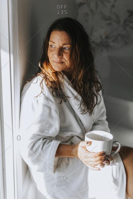 Woman holding mug looking away
