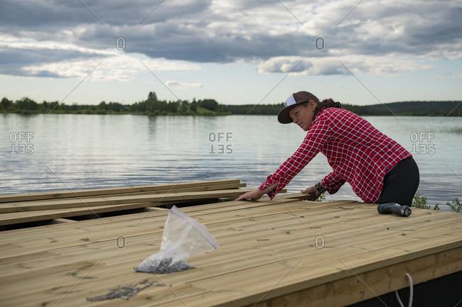 Woman doing carpentry at lake