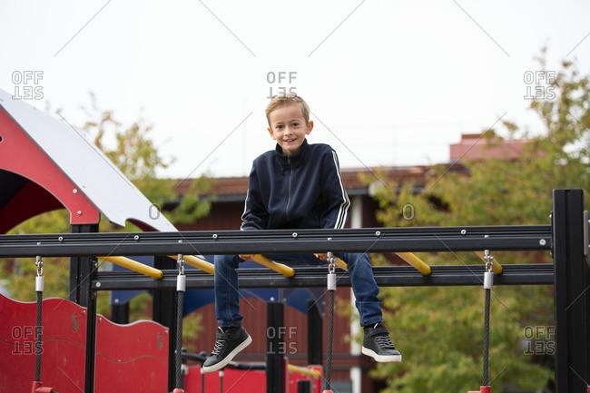 Boy sitting on monkey bars