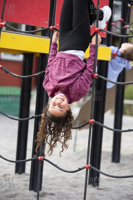 Girl playing on climbing frame