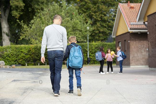 Father taking boy to school