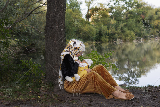 Mother breastfeeding baby at lake