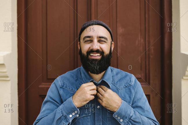 Smiling man standing against door