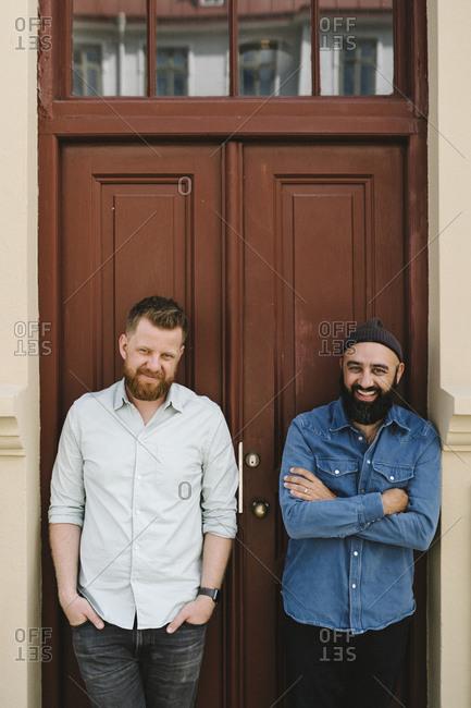 Men standing against brown door