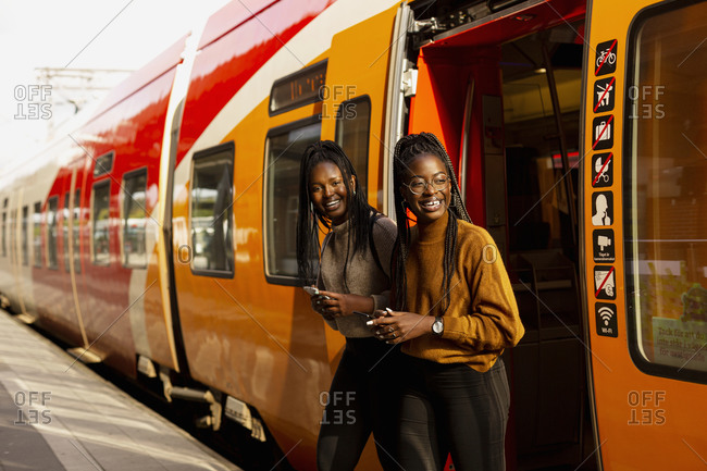 Smiling female friends leaving train