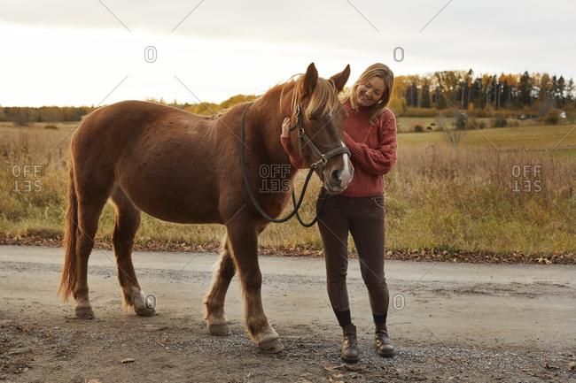 Woman stroking horse in farm