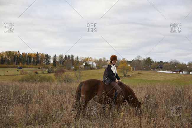 Girl riding horse in farm