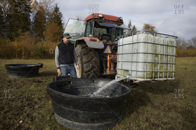 Farmer pouring water for animals