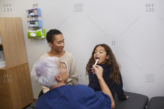 Female doctor checking girls throat