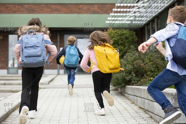 Rear view of schoolchildren running