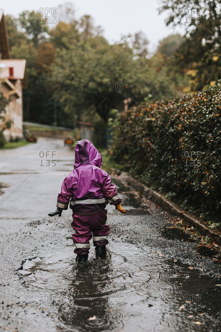 Toddler girl wading in puddle
