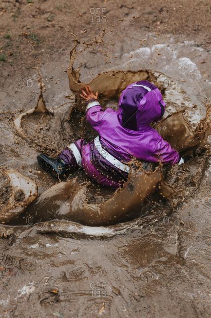 Toddler girl splashing in puddle