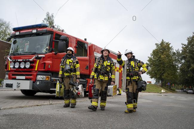 Firefighters walking, fire engine in background