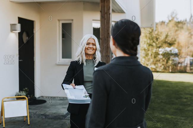 Female estate agent showing woman documents