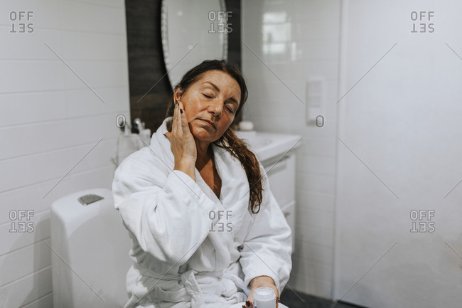 Woman applying moisturizer on her face