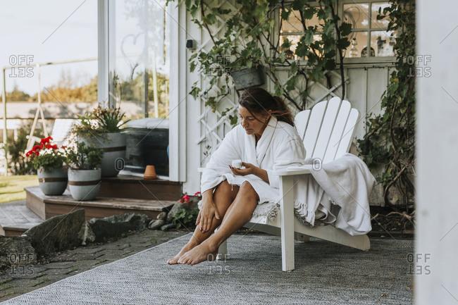 Woman applying moisturizer on her leg