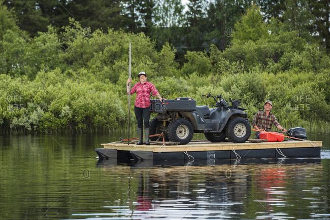 Couple transporting quadbike on motor raft