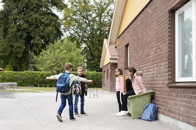 Smiling children in front of school