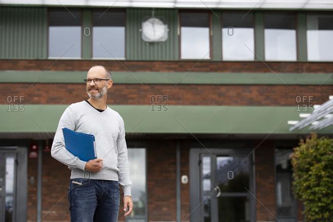Teacher standing in front of school