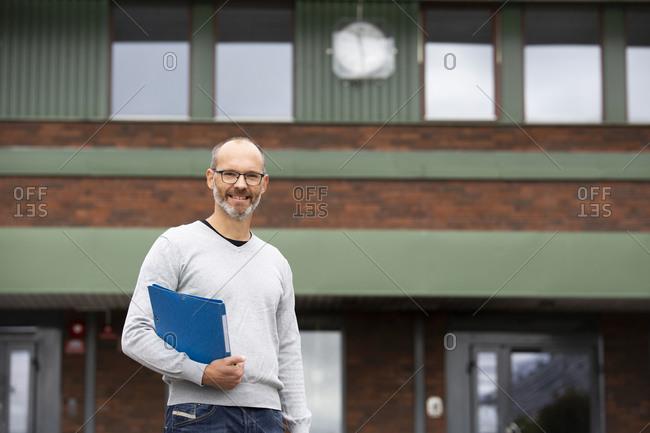 Smiling teacher in front of school