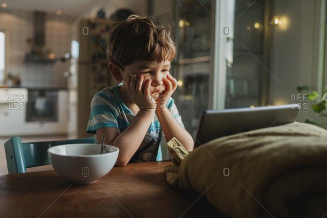Bored boy looking at digital tablet