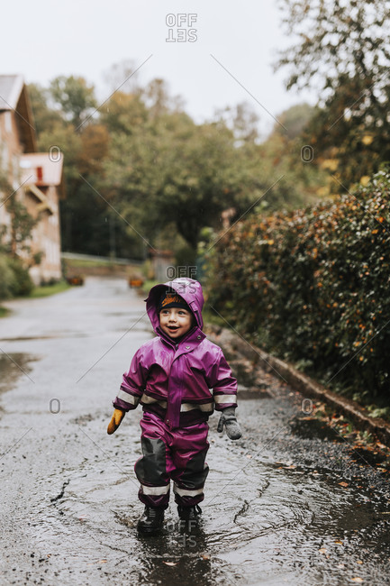 Happy toddler girl standing in puddle