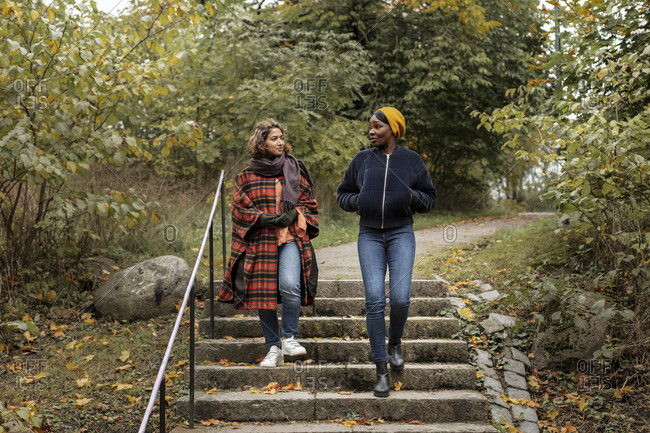 Two young women walking in park