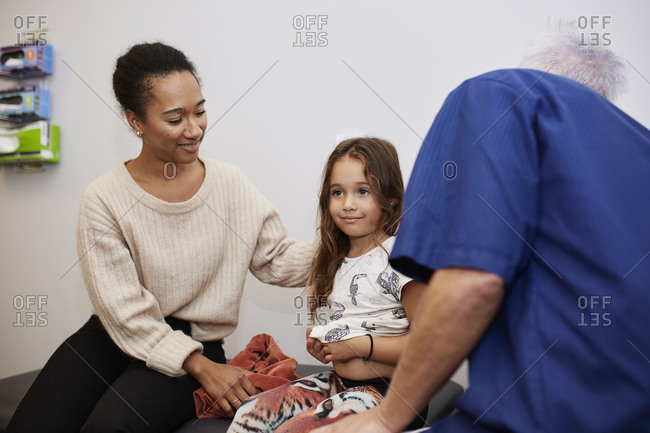 Doctor examining girl in health center