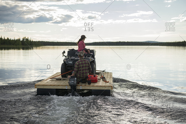 Couple transporting quadbike on motor raft