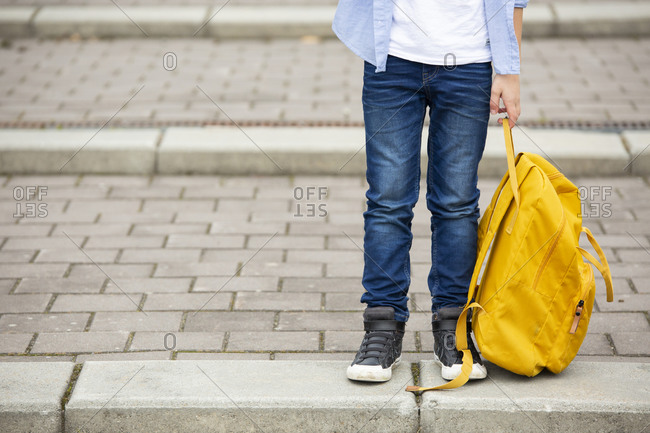 Low section of boy holding backpack