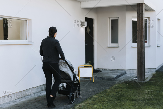 Woman with pram in front of house