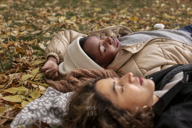 Female friends relaxing on blanket at autumn