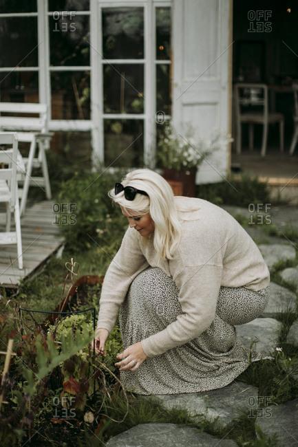 Woman taking care of plants in garden