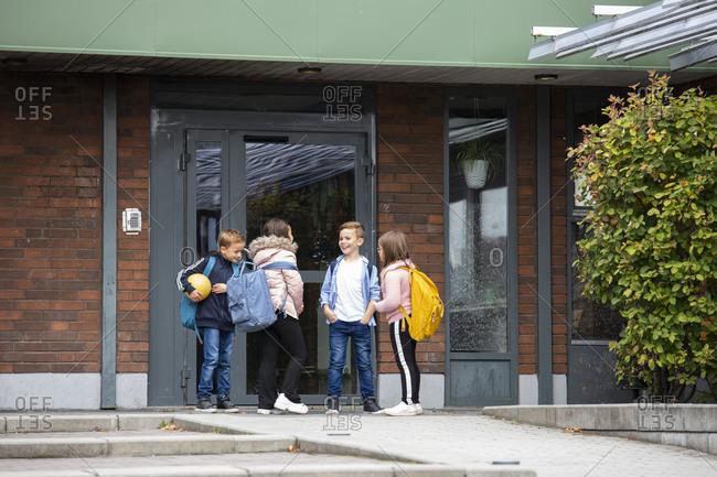 Children talking in front of school building