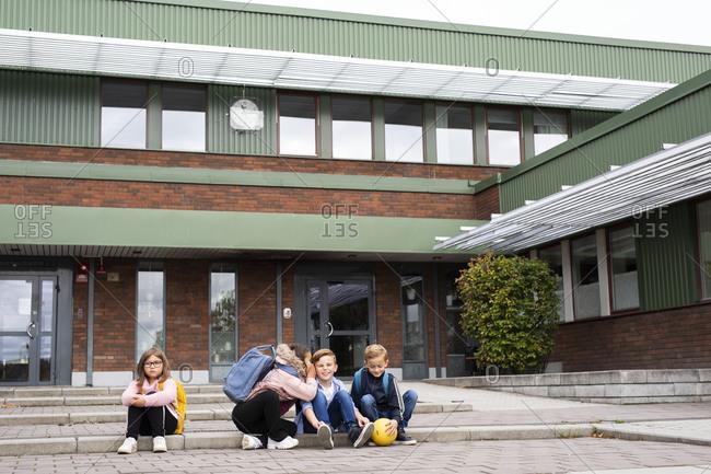 Children sitting in front of school building