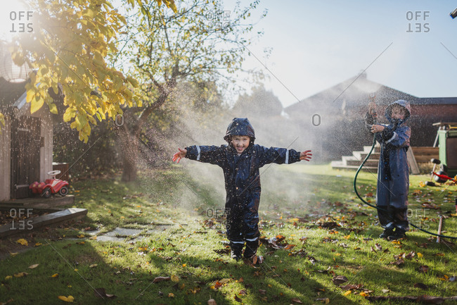 Children playing in garden with garden hose