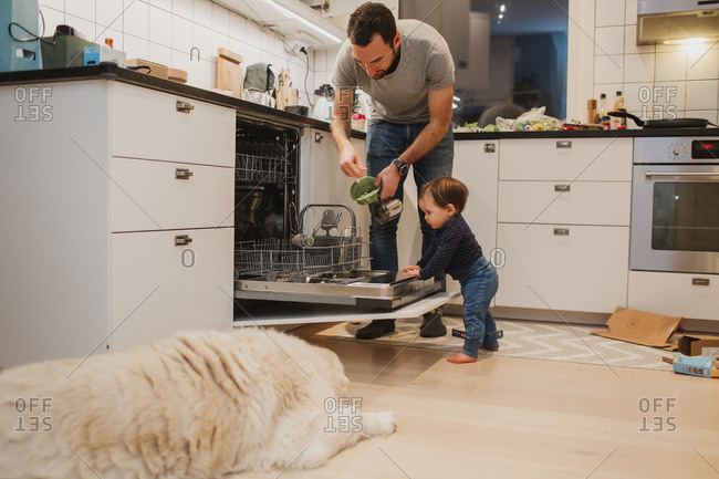 Father with toddler putting dishes into dishwasher