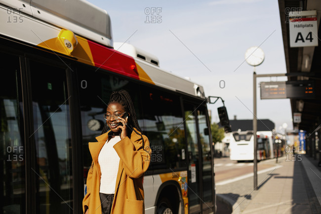 Smiling woman using phone at bus station