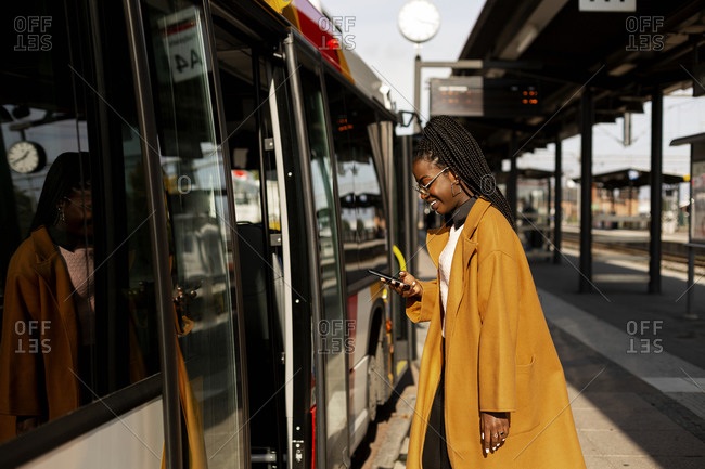 Smiling woman using phone while entering bus