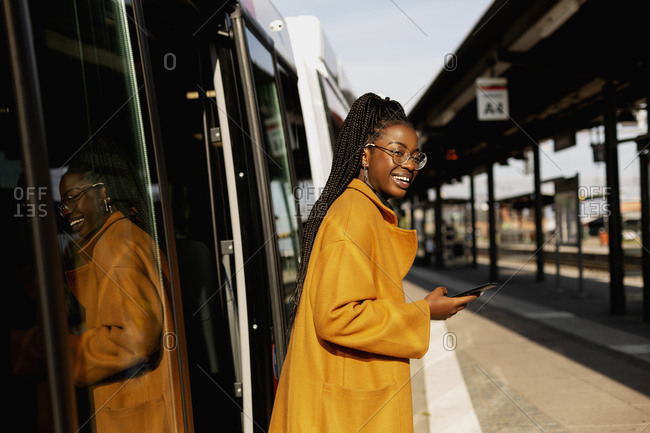 Smiling woman leaving bus at bus station