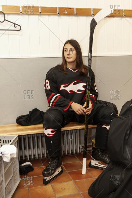 Girl hockey player sitting in locker room