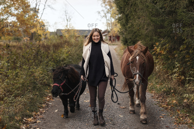 Woman walking with horses on country road