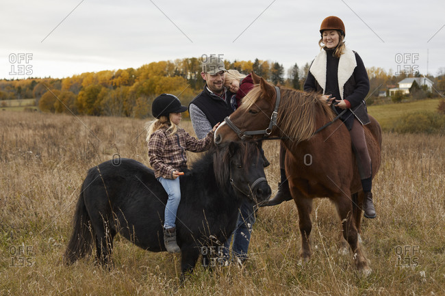 Girl with parents riding horses in farm