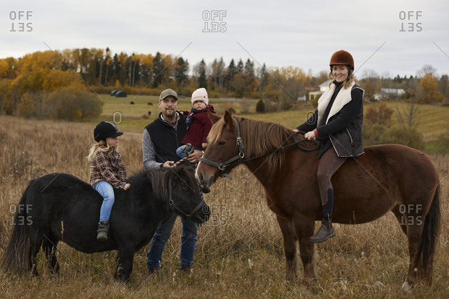 Girls with parents riding horses in farm