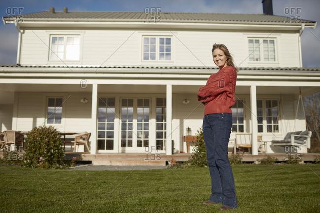 Young woman standing in front of house