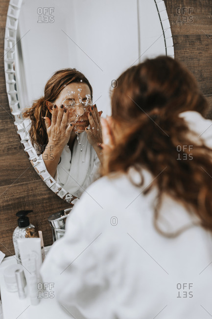 Woman washing her face in front of mirror