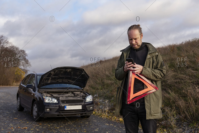 Man using cell phone while holding warning triangle
